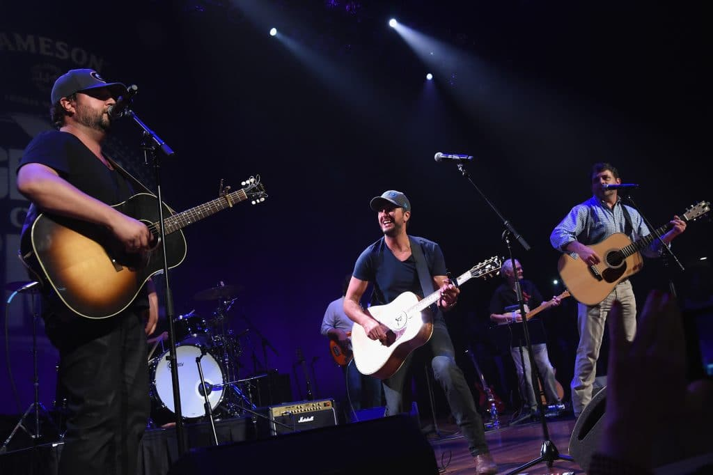 Luke Bryan joins the Peack Pickers, Dallas Davidson, Rhett Akins and Ben Hayslip, on stage at the Ryman during the 3rd Annual Jameson Irish Whiskey Presents Georgia On My Mind. (Photo by Rick Diamond/Getty Images)